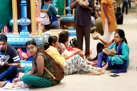 side the main temple, devotees are eating packaged vegetarian food sitting on the floor